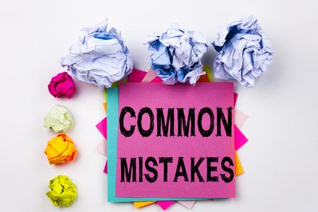 オフィスの付箋に書かれた一般的な間違いを示すテキストをねじ紙のボールで書きます。孤立した背景における一般的な意思決定ミスのビジネスコ 写真素材