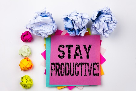 Writing text showing Stay Productive written on sticky note in office with screw paper balls. Business concept for Concentration Efficiency Productivity on white isolated background. Stock Photo