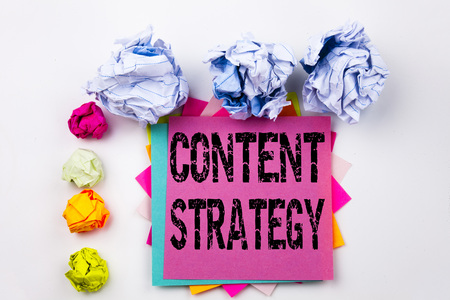 Writing text showing Content Strategy written on sticky note in office with screw paper balls. Business concept for Network Website Information Management on white isolated background.
