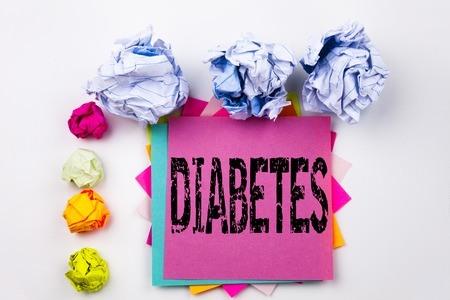 Writing text showing Diabetes written on sticky note in office with screw paper balls. Business concept for Disease Medical Insulin the white isolated background.