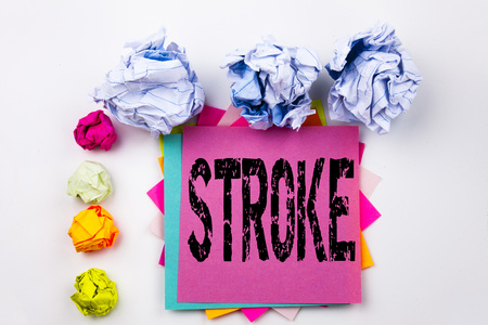 Writing text showing Stroke written on sticky note in office with screw paper balls. Business concept for Medicine health stethoscope illness the white isolated background. Stock Photo