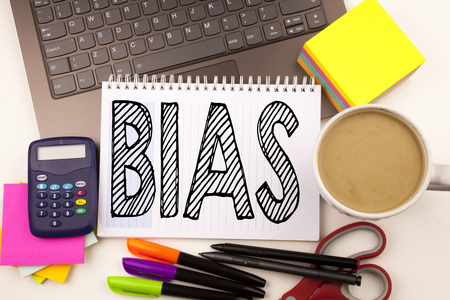 Word writing Bias in the office with laptop, marker, pen, stationery, coffee. Business concept for Prejudice Biased Unfair Treatment Workshop white background with space Фото со стока