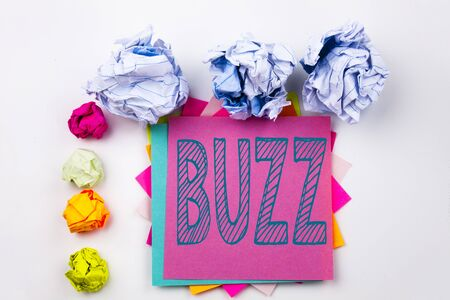 Writing text showing Buzz written on sticky note in office with screw paper balls. Business concept for Buzz Word llustration on white isolated background.