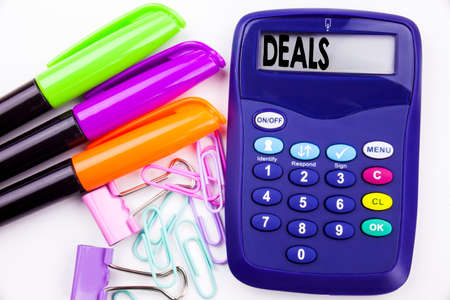 Writing word Deals text in the office with surroundings such as marker, pen writing on calculator. Business concept for Advertising Deal white background with space
