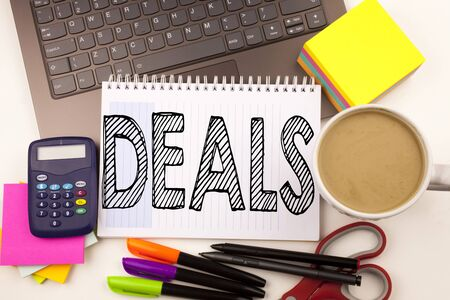 Word writing Deals in the office with laptop, marker, pen, stationery, coffee. Business concept for Advertising Deal Workshop white background with space Stock Photo
