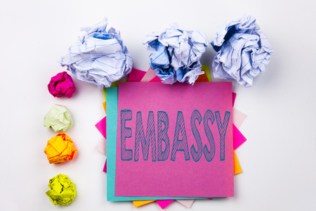 Writing text showing Embassy written on sticky note in office with screw paper balls. Business concept for Tourist Visa Application on white isolated background. Stock Photo