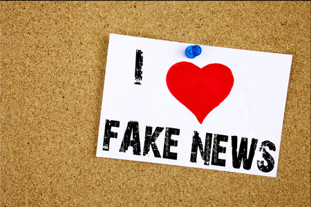 Hand writing text caption inspiration showing I Love Fake News concept meaning Fake News Loving written on sticky note, reminder isolated background with space