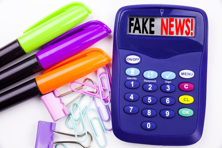 Writing word Fake News text in the office with surroundings such as marker, pen writing on calculator. Business concept for Propaganda Newspaper Fake News white background with space