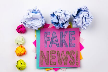 Writing text showing Fake News written on sticky note in office with screw paper balls. Business concept for Propaganda Newspaper Fake News on white isolated background. Stock Photo