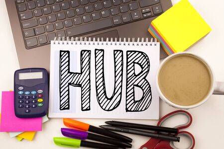 Word writing HUB in the office with laptop, marker, pen, stationery, coffee. Business concept for HUB Advertisement Workshop white background with space