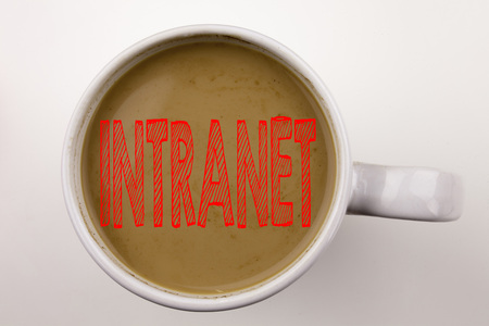Word, writing Intranet word cloud text in coffee in cup. Business concept for Internet Network Technology on white background with space. Black text with red word. Stock Photo