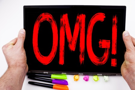 OMG Oh My God text written on tablet, computer in the office with marker, pen, stationery. Business concept for Surprise Humor white background with space