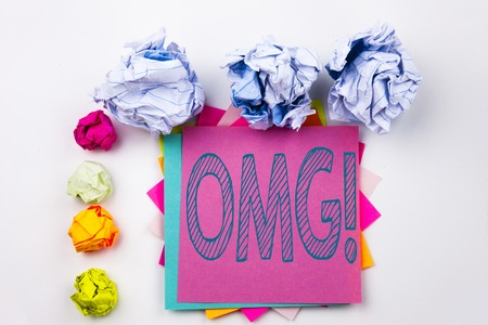Writing text showing OMG Oh My God written on sticky note in office with screw paper balls. Business concept for Surprise Humor on white isolated background. Stock Photo