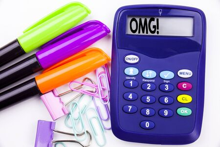 Writing word OMG Oh My God text in the office with surroundings such as marker, pen writing on calculator. Business concept for Surprise Humor white background with space