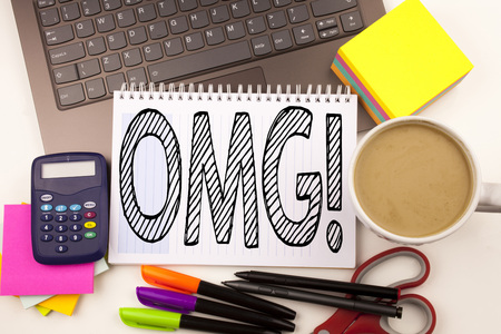 Word writing OMG Oh My God in the office with laptop, marker, pen, stationery, coffee. Business concept for Surprise Humor Workshop white background with space Stock Photo