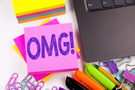 Writing text showing OMG Oh My God made in the office with surroundings such as laptop, marker, pen. Business concept for Surprise Humor Workshop white background space