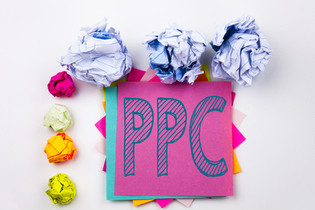 Writing text showing PPC - Pay per Click written on sticky note in office with screw paper balls. Business concept for Internet SEO Money the white isolated background.