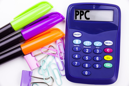 Writing word PPC - Pay per Click text in the office with surroundings such as marker, pen writing on calculator. Business concept for Internet SEO Money white background with space Stock Photo