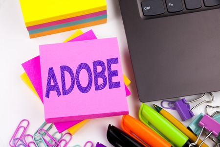 Writing text showing ADOBE made in the office with surroundings such as laptop, marker, pen. Business concept for Software Company Name Workshop white background space