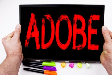 ADOBE text written on tablet, computer in the office with marker, pen, stationery. Business concept for Software Company Name white background with space