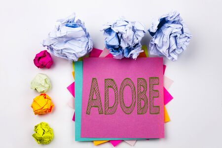 Writing text showing ADOBE written on sticky note in office with screw paper balls. Business concept for Software Company Name on white isolated background.