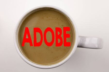 Word, writing ADOBE text in coffee in cup. Business concept for Software Company Name on white background with space. Black text with red word. 写真素材