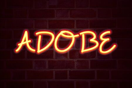 ADOBE neon sign on brick wall background. Fluorescent Neon tube Sign on brickwork Business concept for Software Company Name 3D rendered Front View 写真素材