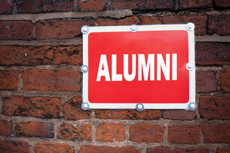 Hand writing text caption inspiration showing Alumni Former Students concept meaning Celebration Education Ending written on old announcement road sign with background and space