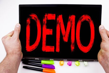 Demo text written on tablet, computer in the office with marker, pen, stationery. Business concept for Software Demonstration white background with space Stock Photo