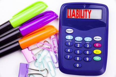 Writing word Liability text in the office with surroundings such as marker, pen writing on calculator. Business concept for Accountability Legal Blame Risk white background with space 스톡 콘텐츠