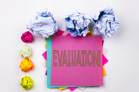 Writing text showing Evaluation written on sticky note in office with screw paper balls. Business concept for Assessment Employee Performance Feedback  on white isolated background. Stock Photo