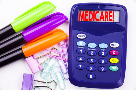 Writing word Medicare text in the office with surroundings marker, pen writing on calculator. Business concept for Comprehensive Medical Insurance Health Plan white background with space