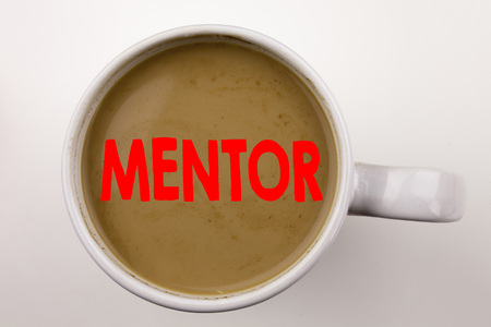 Word, writing Mentor text in coffee in cup. Business concept for Guide Teacher Coach Instructor Counsellor Tutor on white background with space. Black text with red word.