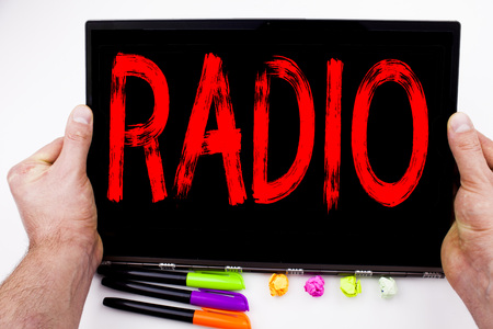 Radio text written on tablet, computer in the office with marker, pen, stationery. Business concept for Media and Education white background with space