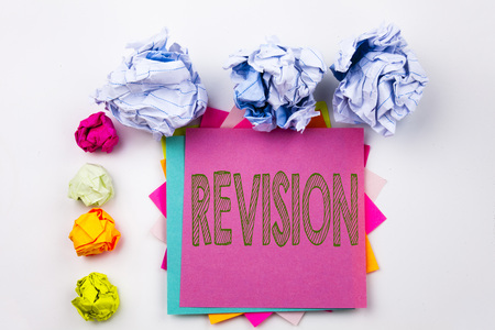 Writing text showing Revision written on sticky note in office with screw paper balls. Business concept for Repeat Repetition Education Material for Exam on white isolated background.
