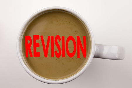 Word, writing Revision text in coffee in cup. Business concept for Repeat Repetition Education Material for Exam on white background with space. Black text with red word. Stock Photo