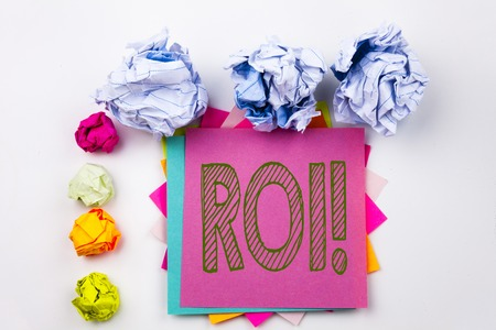 Writing text showing ROI written on sticky note in office with screw paper balls. Business concept for Return On Investment on white isolated background.