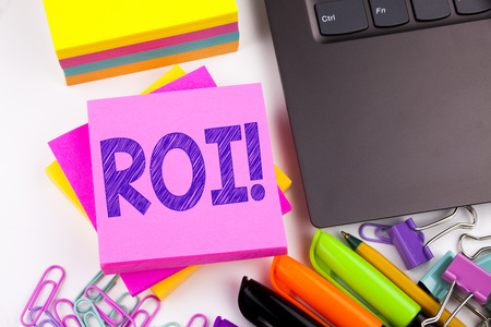Writing text showing ROI made in the office with surroundings such as laptop, marker, pen. Business concept for Return On Investment Workshop white background space