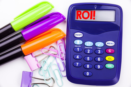 Writing word ROI text in the office with surroundings marker, pen writing on calculator. Business concept for Return On Investment white background with space