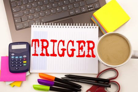 Word writing Trigger in the office with  laptop, marker, pen, stationery, coffee. Business concept for Stir Spark Loose or Unleash Idea Workshop white background with space Stock Photo