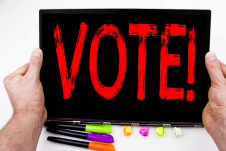 Vote text written on tablet, computer in the office with marker, pen, stationery. Business concept for Voting Electoral Vote white background with space