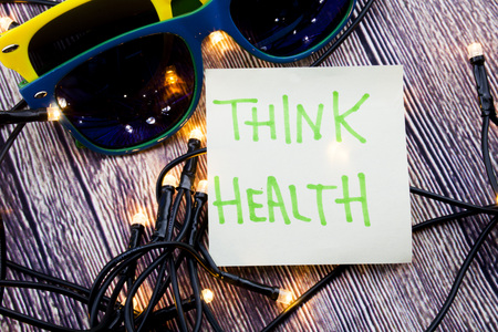 Think Health Sticky note paper with sunglasses, wooden background with lights concept for health awareness