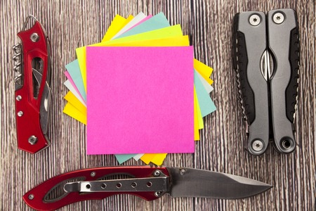sticky note with empty space for a text on wooden background. Hunting health emotional breakdown with knifes