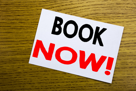 Book Now. Business concept for Reservation Booking written on sticky note, wooden background with copy space.