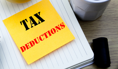 Writing text showing Tax Deductions. Business concept for Finance Incoming Tax Money Deduction written sticky note paper, Wooden background with copy space, Coffee and marker