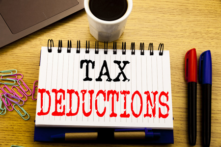 Hand writing text caption showing Tax Deductions. Business concept for Finance Incoming Tax Money Deduction written on notebook on the wooden background in the Office with laptop coffee