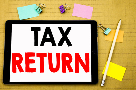 Hand writing text caption inspiration showing Tax Return. Business concept for Accounting Money Return Written on tablet, wooden background with sticky note and pen Stockfoto - 95081849