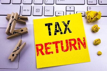 Hand writing text caption inspiration showing Tax Return. Business concept for Accounting Money Return written on sticky paper on the white keyboard background.
