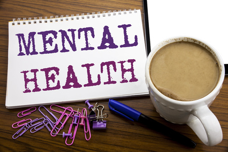Hand writing text caption inspiration showing Mental Health. Business concept for Anxiety Illness Disorder written on note paper on wooden background with coffee and pen 写真素材