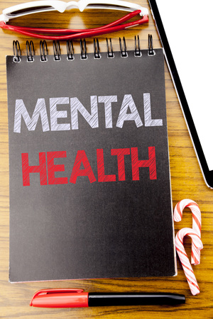 Word, writing Mental Health. Business concept for Anxiety Illness Disorder Written on notebook book, wooden background with sticky sunglasses and red pen